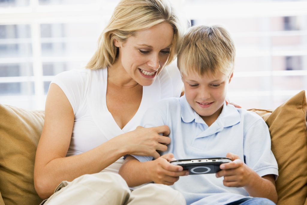 Woman and young boy in living room with handheld video game smil